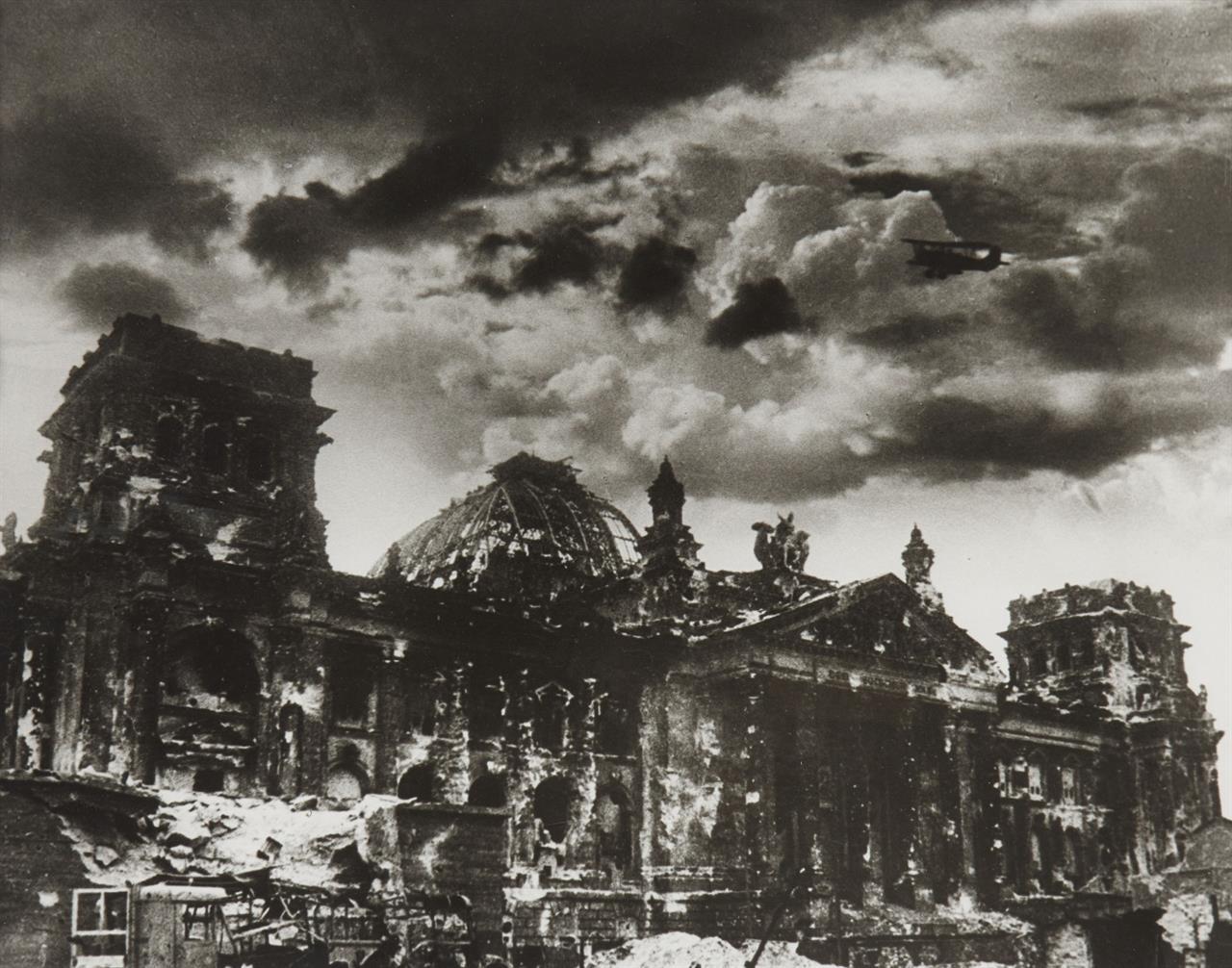 Yevgeni Chaldej. Ein Flugzeug über dem zerstörten Reichstag. (1945). Silbergelatineabzug. Signiert u. datiert. Wohl späterer Abzug.