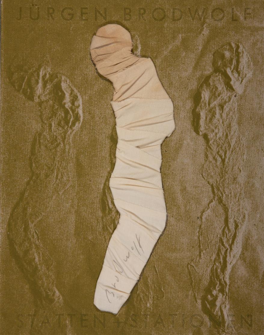 Jürgen Brodwolf. Stätten und Stationen. 1992. Ausstellungskatalog mit bandagierter Pappfigur auf dem Vorderdeckel. Signiert. Ex. 13/50 der VA.