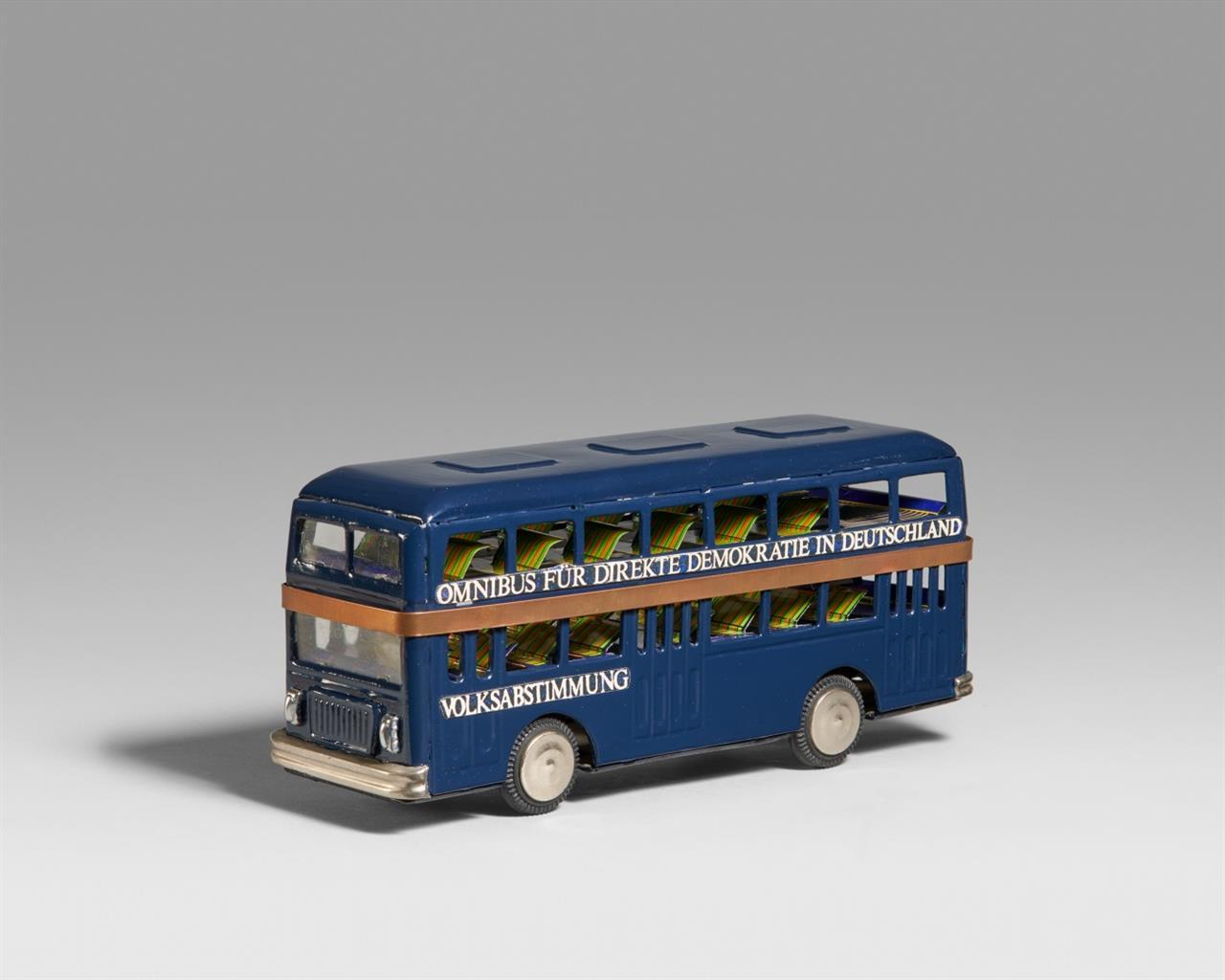 Walther Dahn, Felix Droese, u.a. Omnibus für direkte Demokratie. 1990/91. Multiple, bearbeiteter Spielzeugbus, mit Heft, in Verpackungskarton. Signiert. Ex. 47 von etwa 70 Exemplaren.