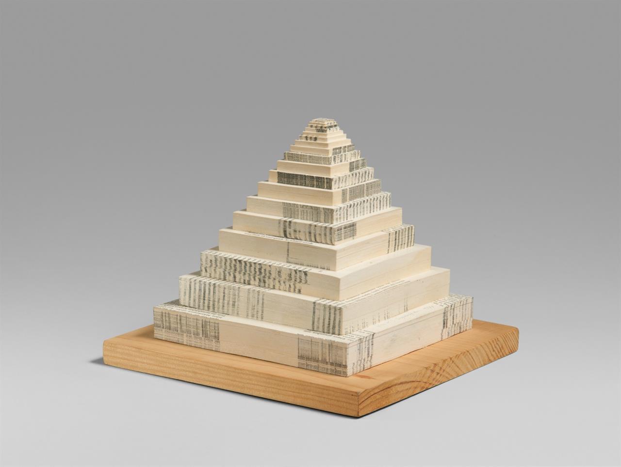 Konrad Balder Schäuffelen. Pyramide. 1980. Bedrucktes Papier, stufenförmig aufeinander geklebt, auf Holzsockel. Signiert. Ex. 2/5.